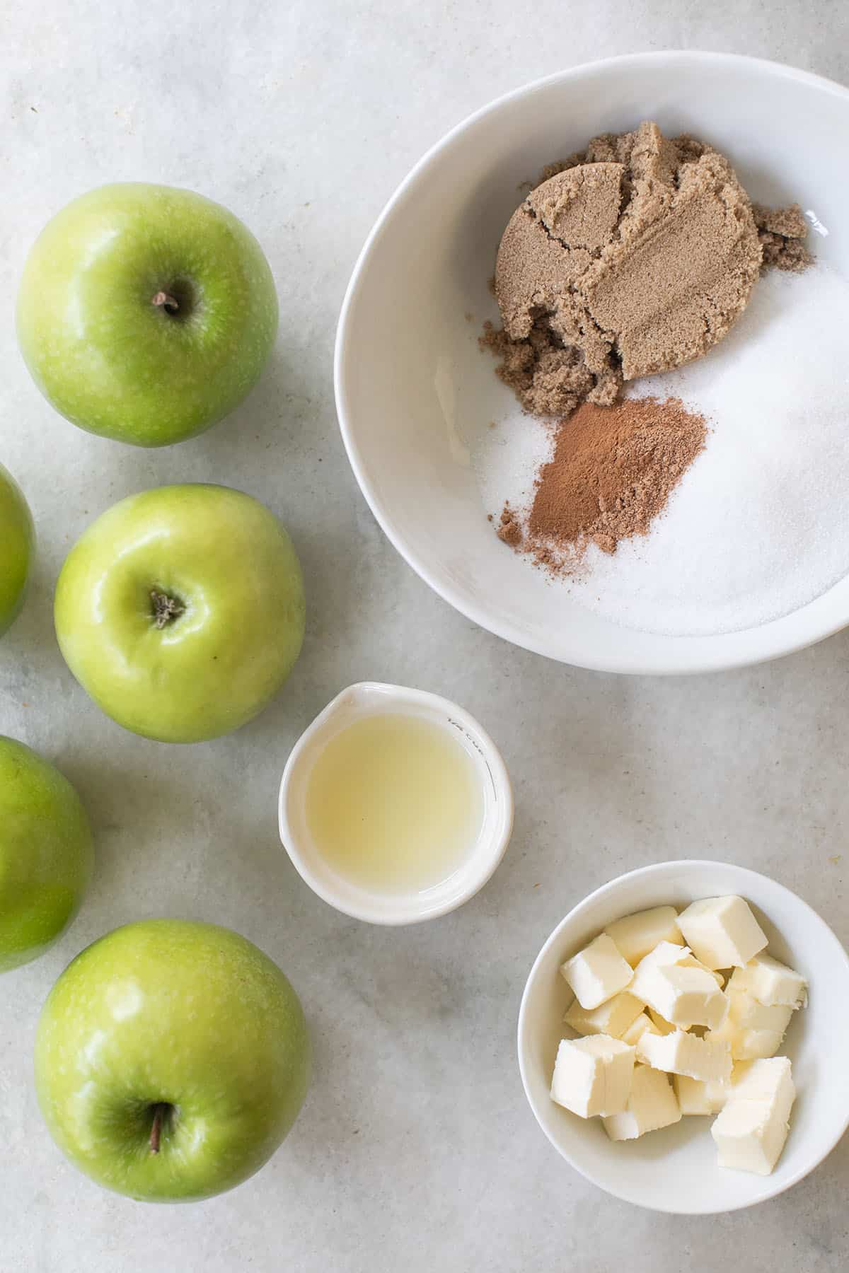 apples, lemon juice, spices, sugar and butter in bowls