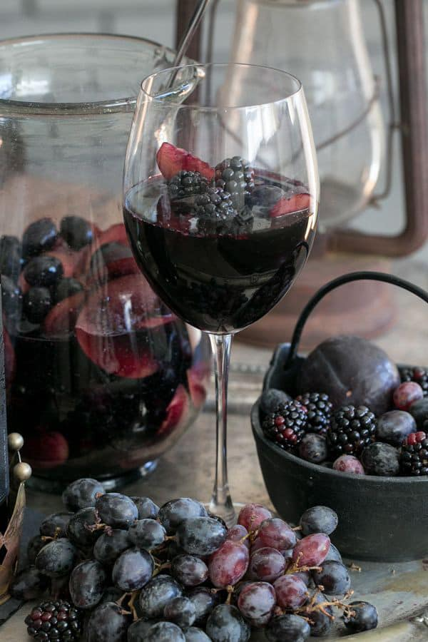 Black sangria in a wine glass with berries.