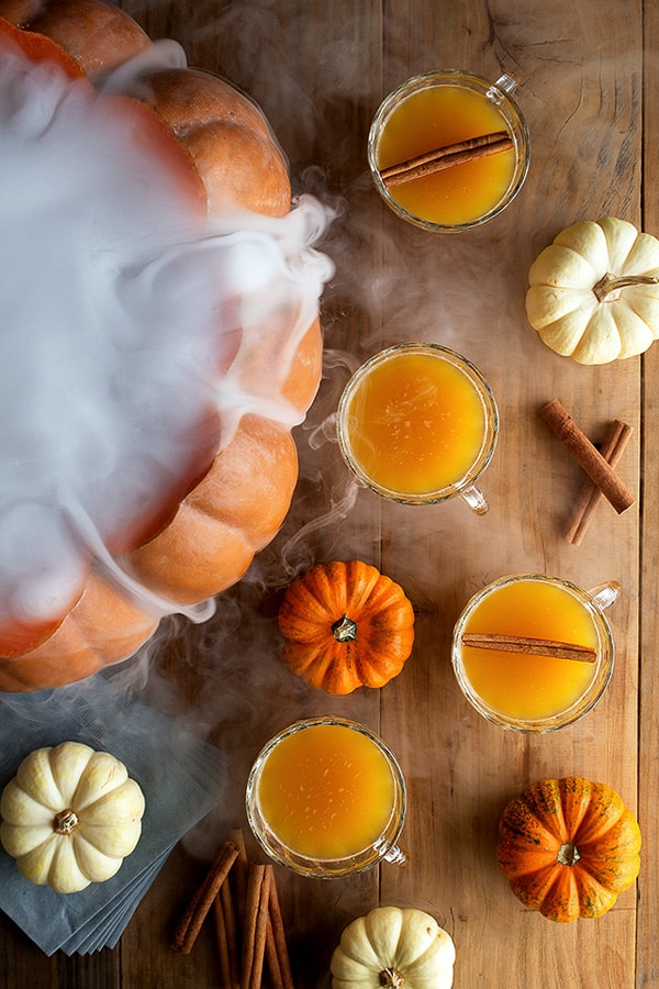 Pumpkin punch in cups with mini pumpkins and a large smoking pumpkin.