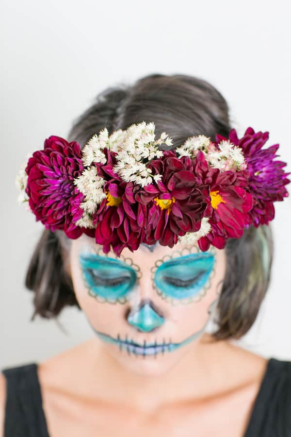 model looking down, wearing a floral crown and easy day of the dead makeup