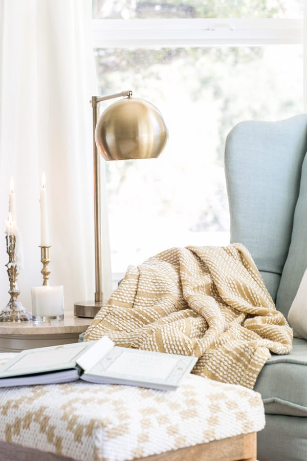 a charming and cozy reading nook with a gold lamp, blue chair and yellow blanket.