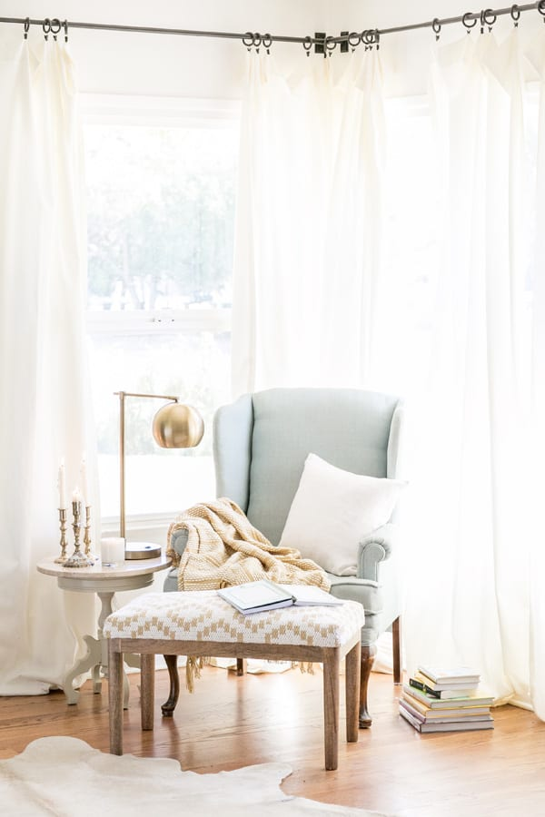 a cozy reading nook with a chair, bench, lamp, pillow and blanket