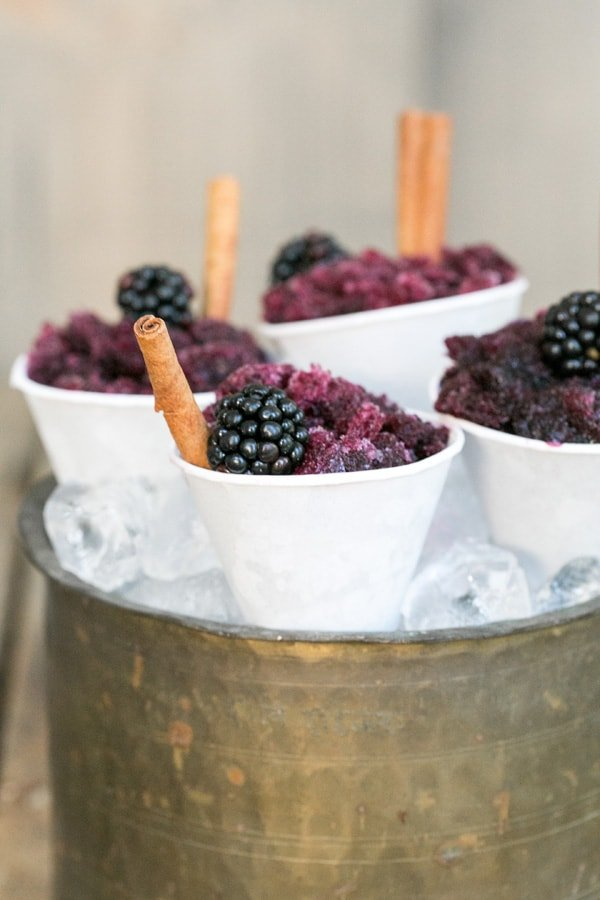 Sangria granita in mini snow cone cups with cinnamon sticks and a blackberry.