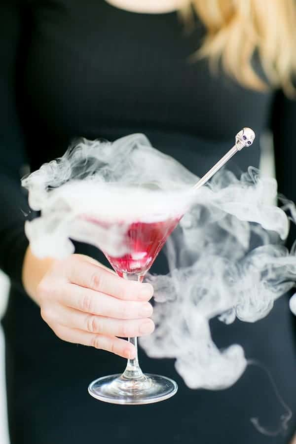Eden Passante holding a blueberry martini smoking with dry ice.