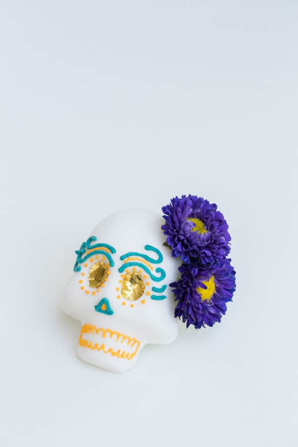 finished project shot of a Mexican sugar skull with purple flowers and gold foil eyes.