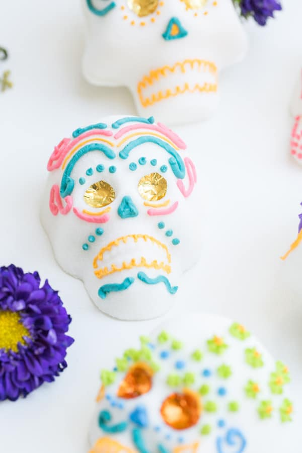 Mexican sugar skull with foil eyes and pink and blue frosting.