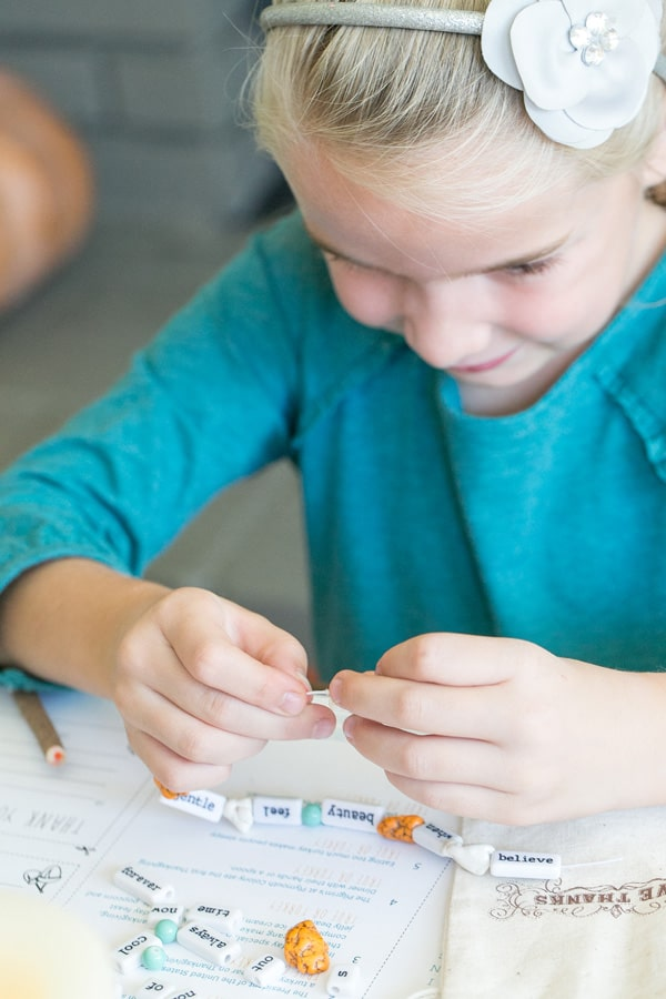 Girl stringing a Thanksgiving craft necklace for kids.