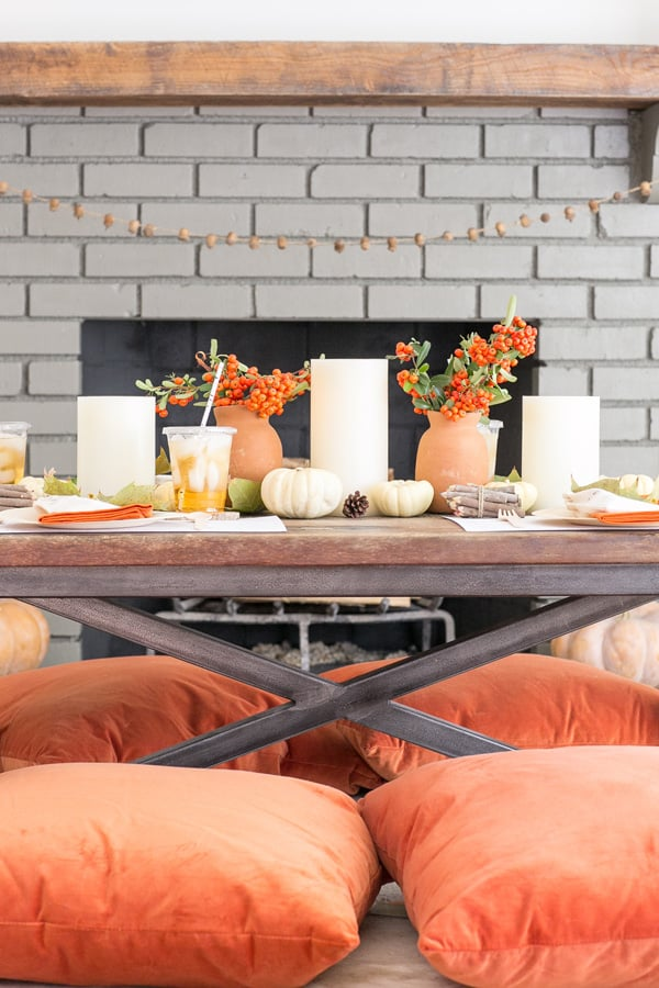 Thanksgiving table set for kids with orange pillows, flowers, games, crafts and more!