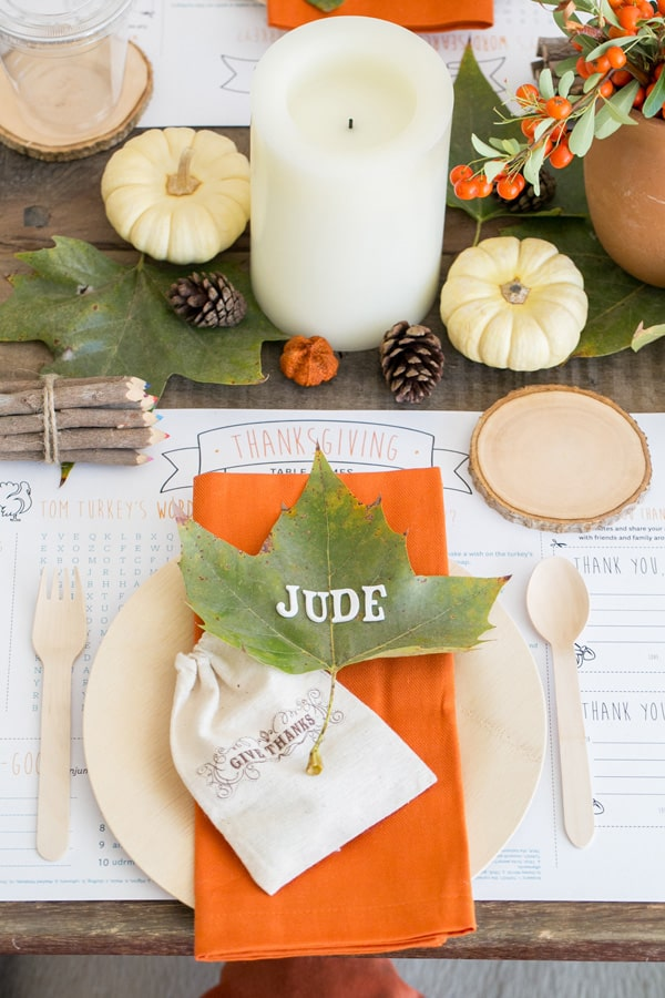 How to set a kids Thanksgiving table. Giant leaf with letter stickers, pumpkins, crayons and bamboo dinnerware.