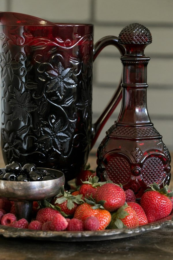 side shot of fruit on a plate with a re pitcher behind