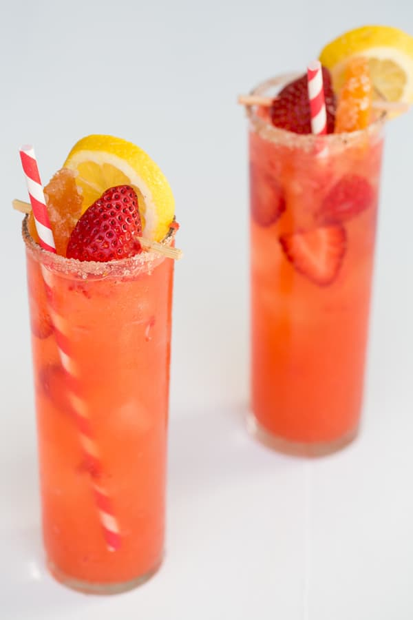 Two grapefruit Collins in a tall glass with strawberry, lemon an da candies grapefruit.