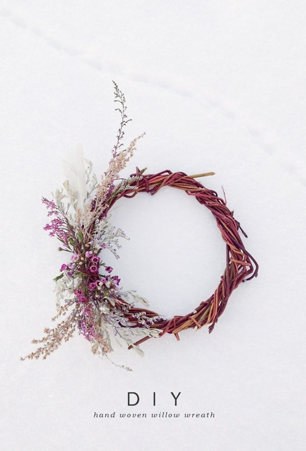 A natural handmade willow wreath in the snow with dried flowers.