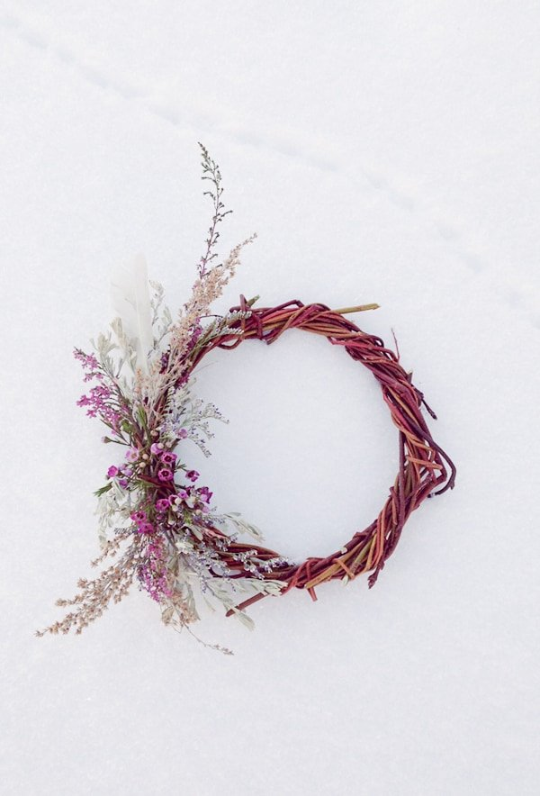 Willow wreath with flowers in the snow.