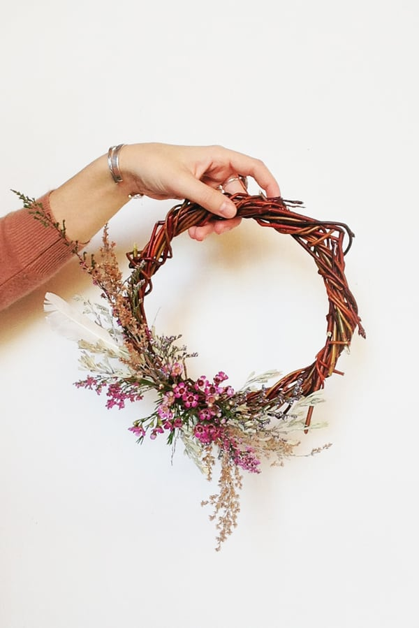 Girl holding a DIY willow wreath with dried flowers on a white wall