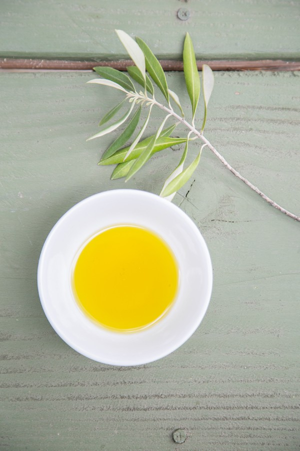 Bowl of olive oil on green table