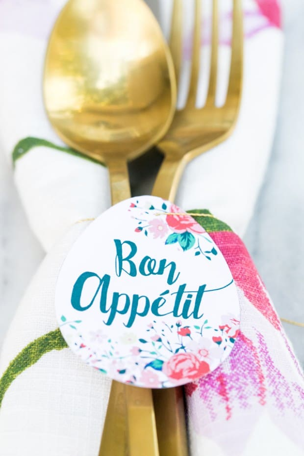 Paper egg shape printable, tied around a napkin and gold flatware.