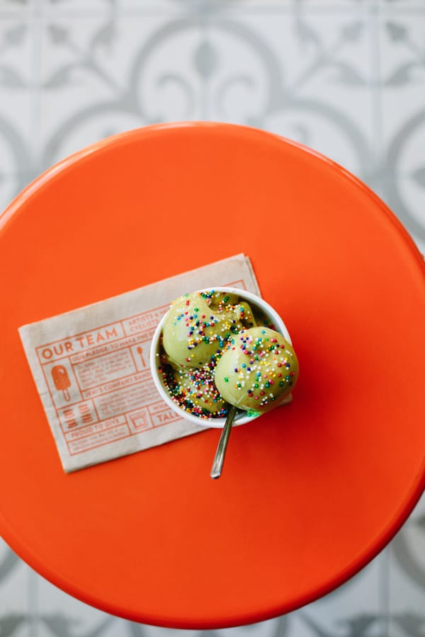 Green ice cream on orange table with sprinkles