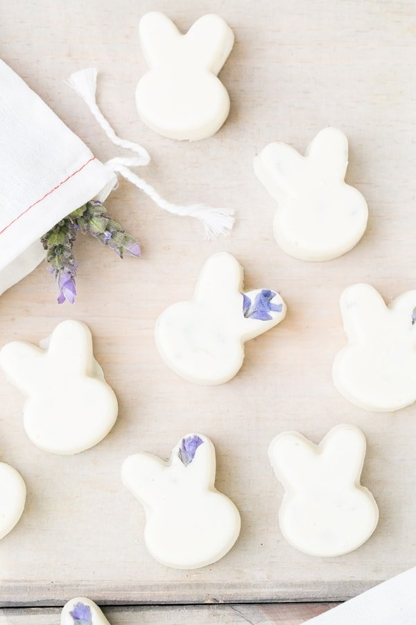 White chocolate bunnies with lavender on a wooden table.