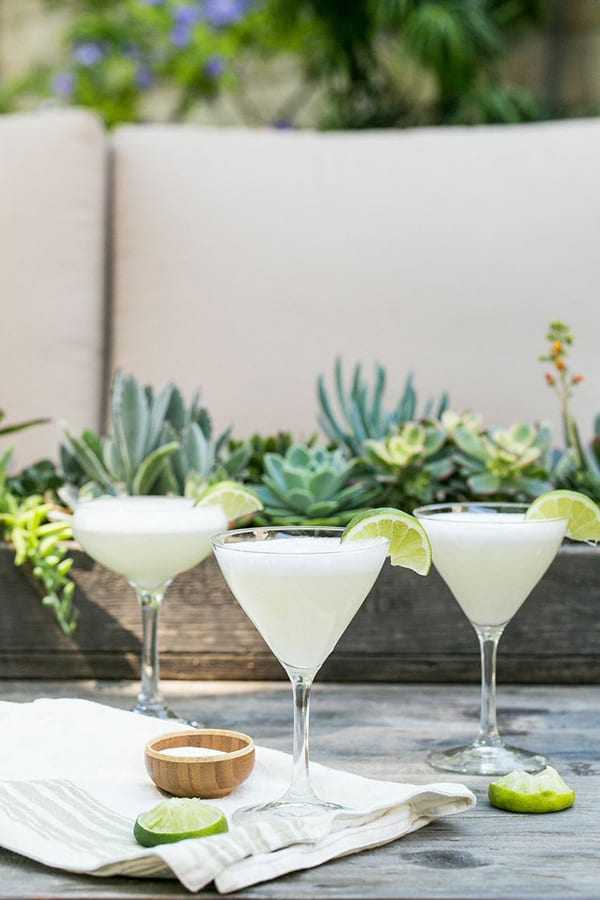 three glasses containing a salt air margarita recipe on a wooden table outside.
