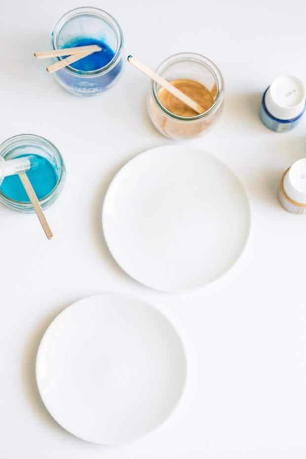 white plate with colored paint in small jars.