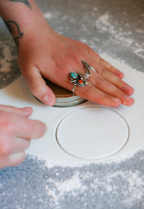 Hand pressing a cookie cutter into fondant