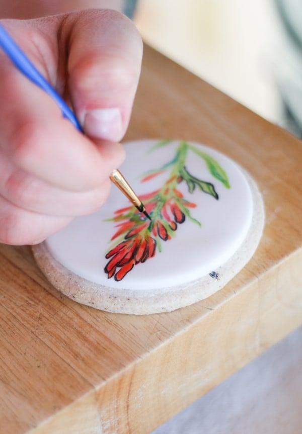 Hand painting flowers on cookies.