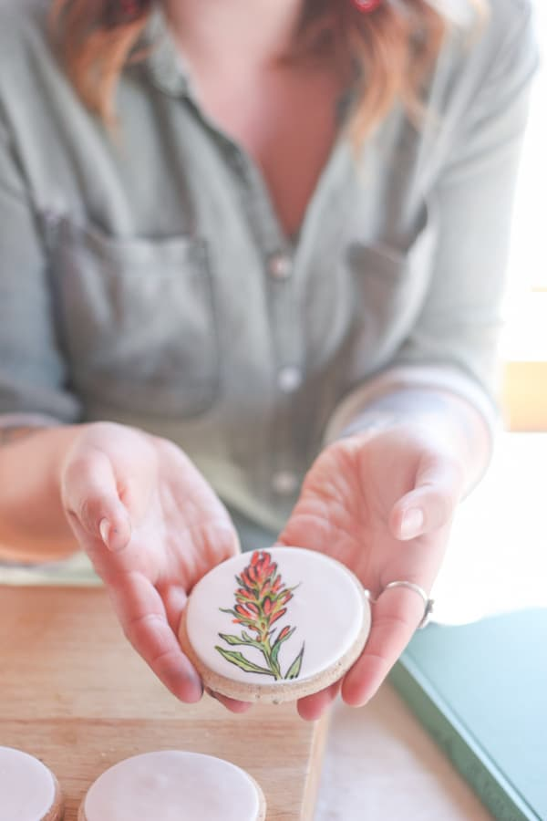 Hand painted flower on a cookie covered in fondant.