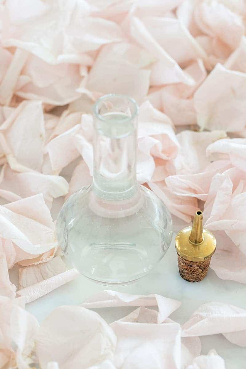 Small bottle of rose water on a table with rose petals.