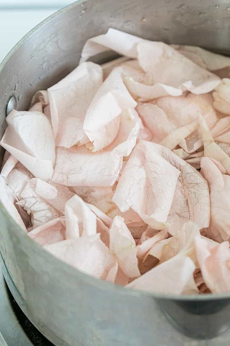 Rose petals simmering in a pot with distilled water.