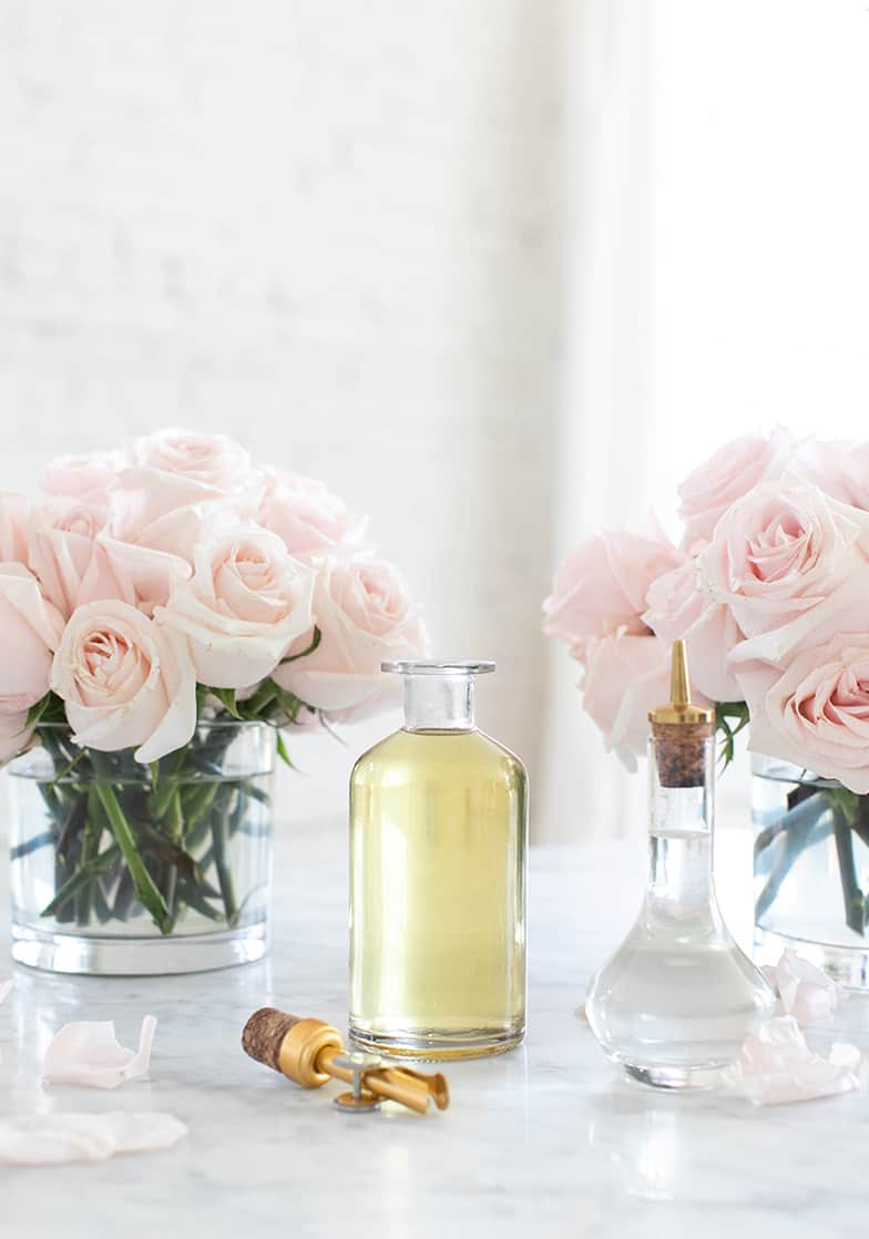 Two bottles of rose water with pink roses in the back.