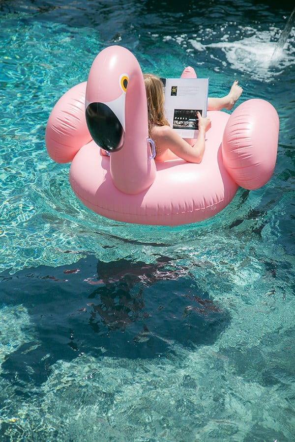 Girl floating on a pink flamingo pool float at a flamingo pool party