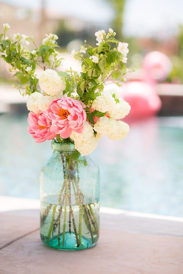 Flower arrangement in a large green glass vase next to a flamingo pool party