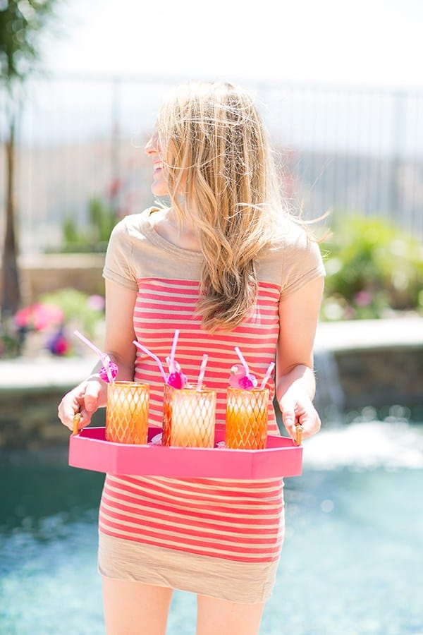 Eden Passante holding a tray of cocktails at a flamingo pool party