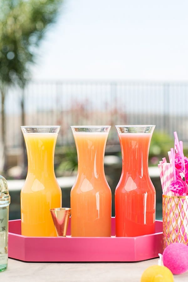 three fresh juices on a pink tray