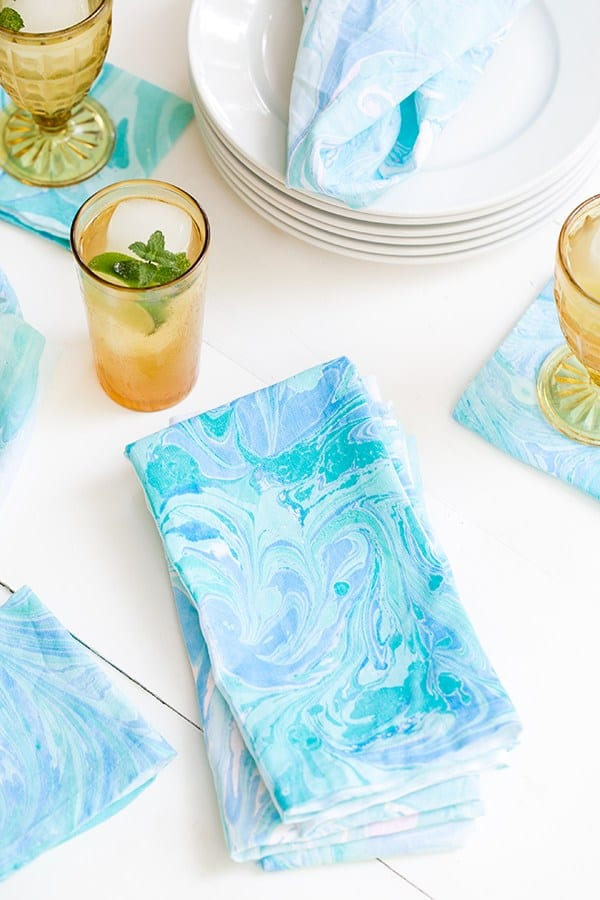 Blue and green marbled fabric napkin with yellow glass.
