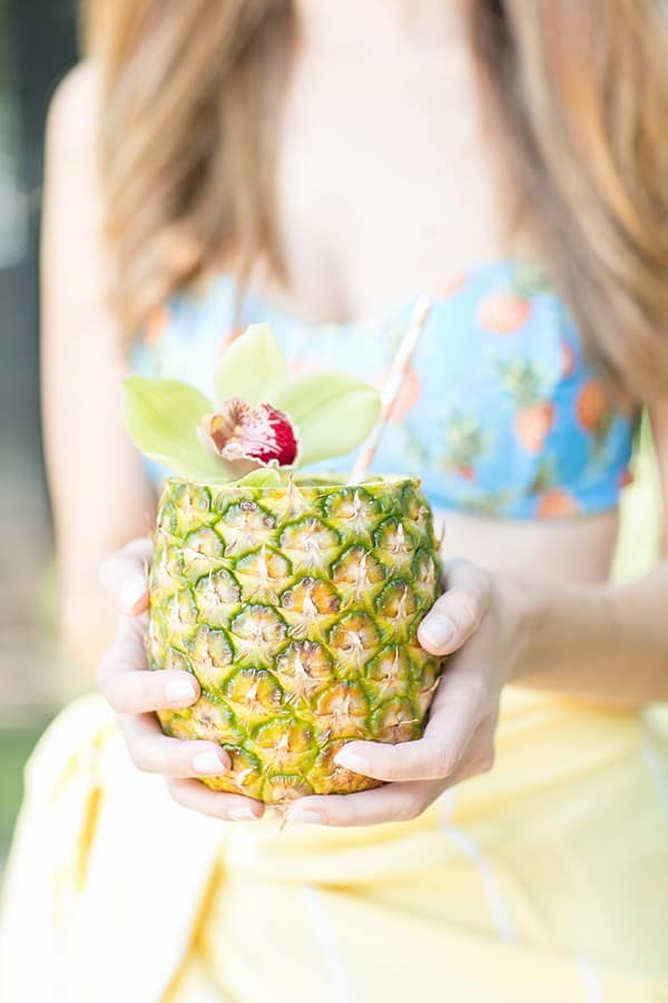 Girl holding a pineapple mojito