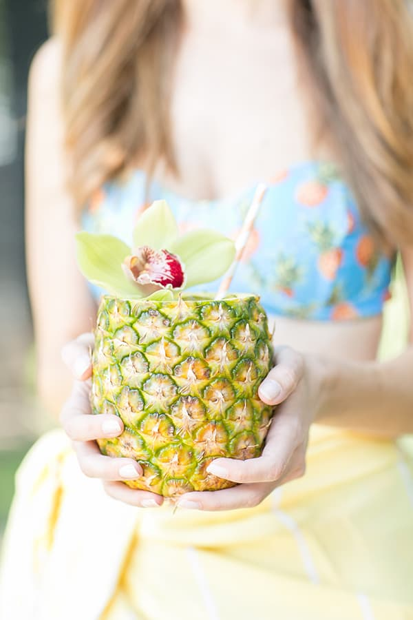 Girl holding a pineapple cocktail.