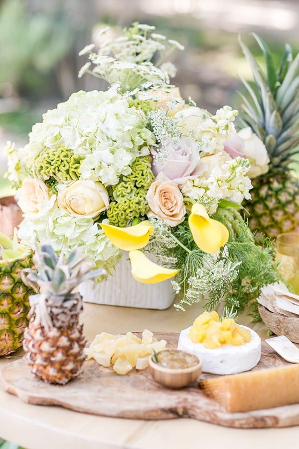 Beautiful tropical flower arrangement on a table with a baby pineapple.