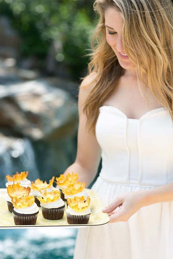 Eden Passante holding a yellow tray with pineapple cupcakes.