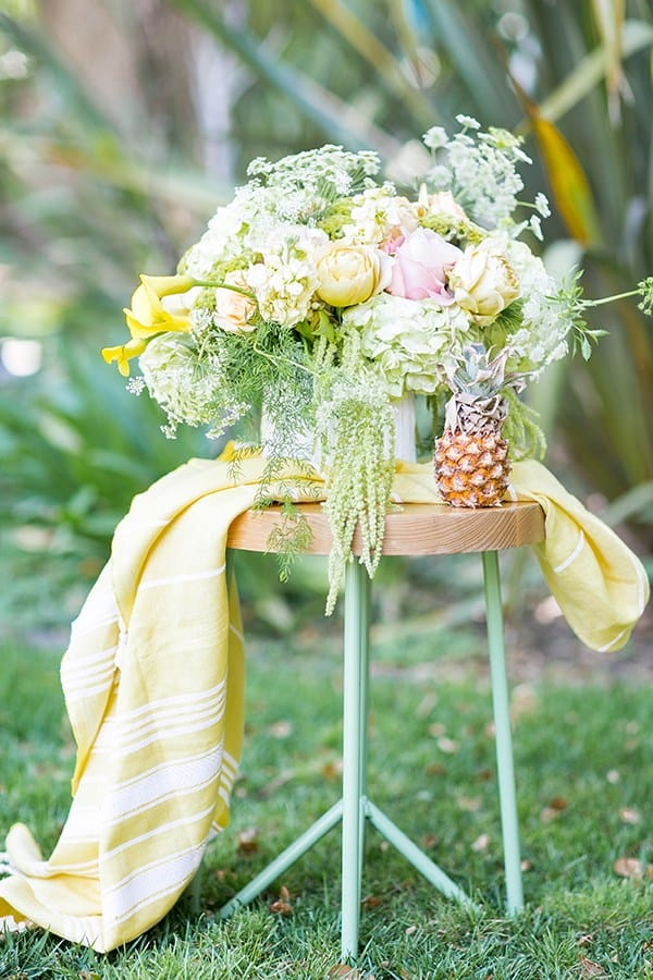 Yellow flowers on a stool with a yellow towel and baby pineapple.