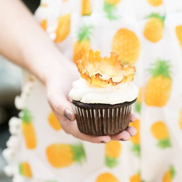 Hand holding a pineapple cupcake.