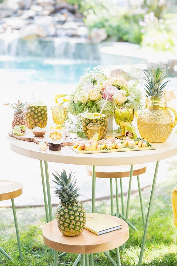A pineapple party set up with food and drinks on a wooden table in front of a pool.