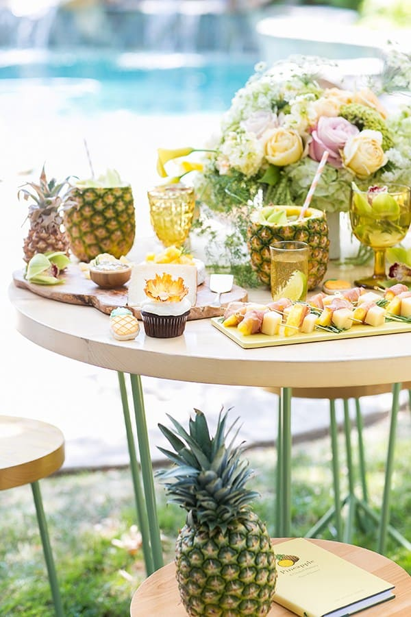 Table with pineapples, flowers, desserts for a pineapple party.