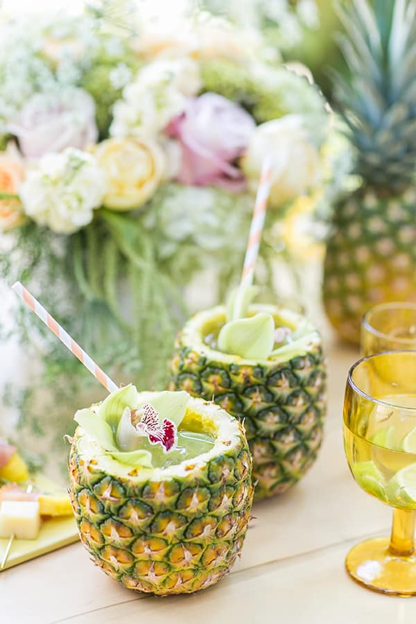 Two pineapples with pineapple mojito inside and straws.