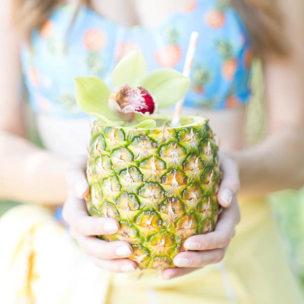 Girl holding a fresh pineapple cocktail.
