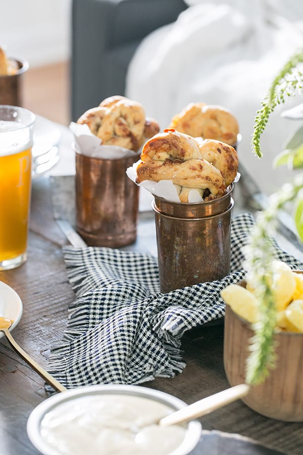 homemade pretzels in a copper cup with cheese dip and beer.