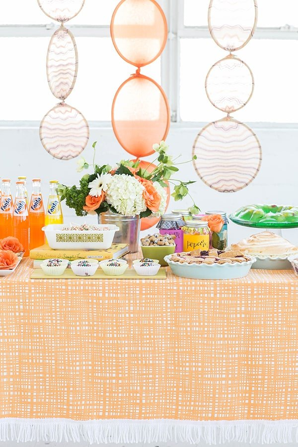 Colorful table full of food and cheesy DIY ideas for an Amy Sedaris Halloween party