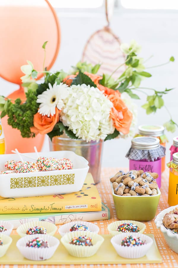 Amy Sedaris party with colorful flowers, peanut eyes, books and desserts