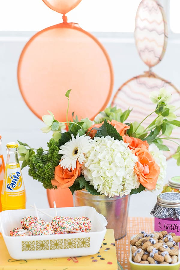 Flowers in tin, Oreo lollipops and colorful party decorations.