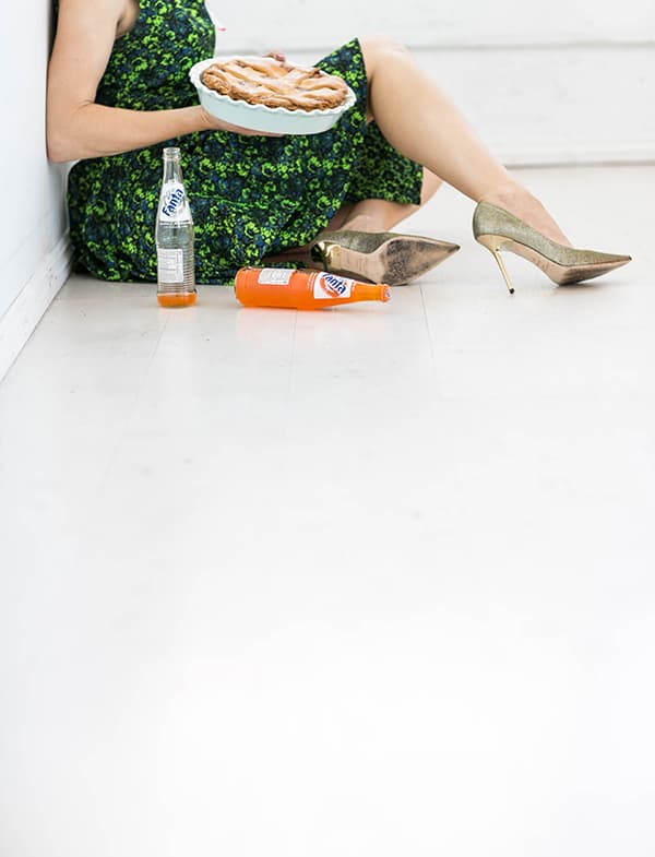 Girl in green dress on the floor holding an apple pie with Fanta nearby.